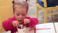 Baby girl in a pink jacket licking cookie with cream - stock footage