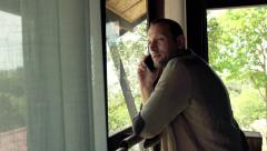 Handsome man talking on cellphone by the window with beautiful garden view   HD Stock Footage