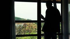 Young man listen to music and dance by the window with beautiful garden view  HD Stock Footage
