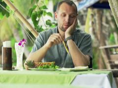 Sad man eating satay chicken in outdoor restaurant with exotic garden NTSC Stock Footage