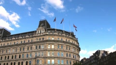 Old building with British flags waving in the wind near Trafalgar Square Stock Footage