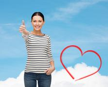 Smiling girl in casual clother showing thumbs up Stock Photos