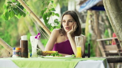 Young sad woman sitting in outdoor restaurant with exotic garden in Thailand HD Stock Footage