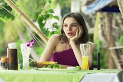 Young sad woman sitting in outdoor restaurant with exotic garden NTSC Stock Footage