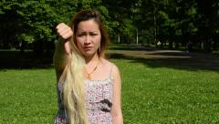 Young attractive asian woman shows thumb down in the park  Stock Footage