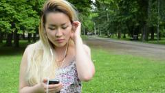 Young attractive happy asian woman listens the music on smartphone in the park  Stock Footage