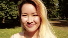 Young asian attractive happy woman in the park - smiles to camera - detail Arkistovideo