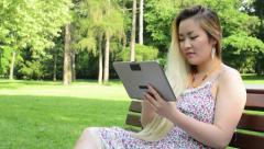 Young asian attractive happy woman sits on bench in the park-work on tablet Stock Footage