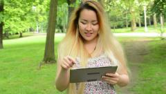 Young asian attractive woman uses tablet - walks in the park - steadicam Stock Footage