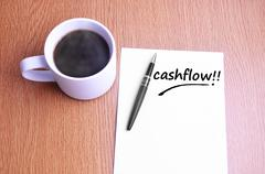 Coffee, pen and notes write cashflow Stock Photos