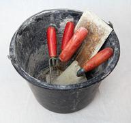 Bucket with masonry tools - stock photo