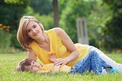 Young beautiful mom and her cute little boy, relaxing and having fun in the p - stock photo