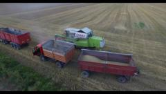 Aerial view of harvester ejects grain into a truck Stock Footage