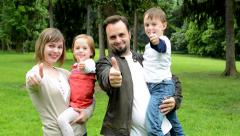 Stock Video Footage of family (middle couple in love, cute girl and small boy) show thumbs on agreement