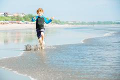 Young boy in swimming shorts and rash vest runs along Bali beach near sunset Stock Photos