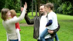 Family (middle couple in love, cute girl and small boy) together give high five Stock Footage