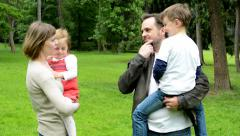 Family (middle couple in love, cute girl and small boy) together talk in park Stock Footage