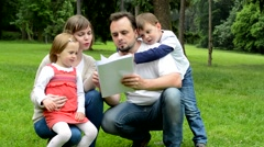 Family (middle couple in love, cute girl and small boy) read document in park Stock Footage