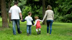 Family (couple in love, girl and boy) walking in park from camera to distance Stock Footage