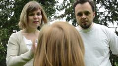 Parents (middle age couple) are angry at a child (girl) - park Stock Footage