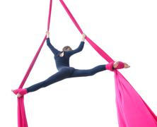 cheerful child training on aerial silks, isolated over white - stock photo