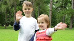 childrens (young boy and little girl (siblings)) wave with hands and smile - stock footage