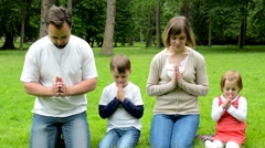 Family (middle aged couple in love, boy and girl) pray in park Arkistovideo