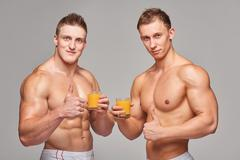 Two athletic men with glasses of orange juice - stock photo