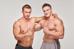 Two athletic men gesturing thumbs up - stock photo