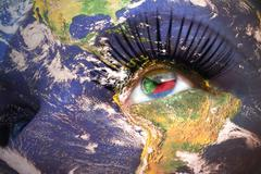 womans face with planet Earth texture and comoros flag inside the eye. - stock photo