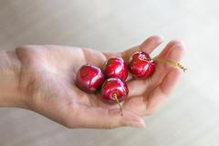 Girl's hand with four cherries - stock photo