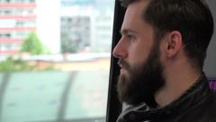 young handsome hipster man travel by train and looks out of the window - city - stock footage