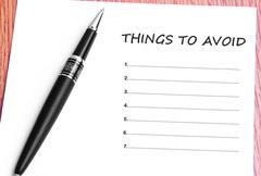Stock Photo of Pen  and notes paper with things to avoid list