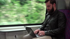 young handsome hipster man travel by train and works on computer (notebook) - stock footage