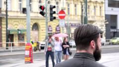 Young handsome hipster man waits in front of pedestrian crossing - urban street Stock Footage