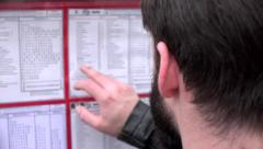Young handsome hipster man looks at the timetables (tram) Stock Footage
