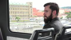 Young handsome hipster man travel by tram - city - building in the background Stock Footage