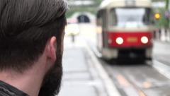Young handsome hipster man look on incoming tram to station in the city - street Stock Footage