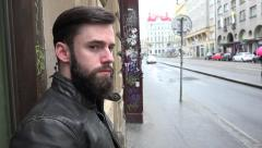 Young handsome hipster man wait on the urban street and looks around - city Stock Footage