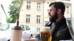 Young handsome hipster man sitting in restaurant (outdoor seating) and looks Stock Footage