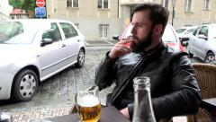 Young handsome hipster man sitting in restaurant (outdoor seating) and smoking Stock Footage