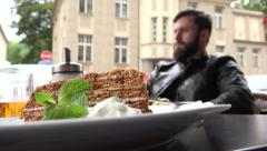 Food - dessert - honey cake - young handsome man (hipster) sitting in background Stock Footage