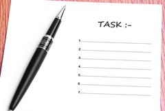 Pen  and notes paper with task list - stock photo