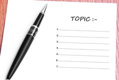 Pen  and notes paper with topic list - stock photo