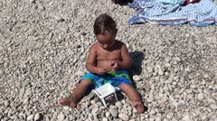 Stout child eating sweet cherries on the beach Stock Footage