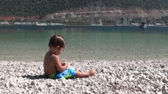 Toddler eating sweet cherries on the beach Stock Footage