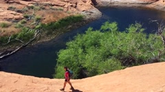 Hiker walking down the slick rock towards small lake Stock Footage