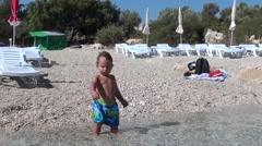 Toddler in long swim shorts- Stock Footage