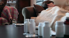 Sick young man on couch with flu and a blanket taking medication - stock footage