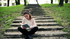 Woman sitting on the stairs in park and reading book Stock Footage